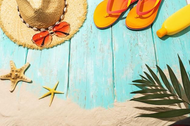 Akcesoria rekreacyjne i piasek na plaży na jasnoniebieskim drewnianym tle z miejscem na kopię pośrodku