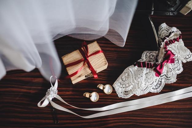 Akcesoria ślubne, sukienka, kolczyki, pudełko i podwiązka leżące na brązowym stole