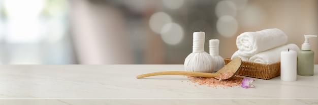 Akcesoria spa z białym ręcznikiem, świecą, aromatycznym olejem, ziołowymi kulkami kompresyjnymi