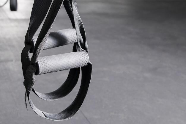 Akcesoria sportowe elementy do ćwiczeń fitness i siłowni dla zdrowych: paski treningowe do pętli. bliska pętla sprzęt do treningu funkcjonalnego na szarym tle.