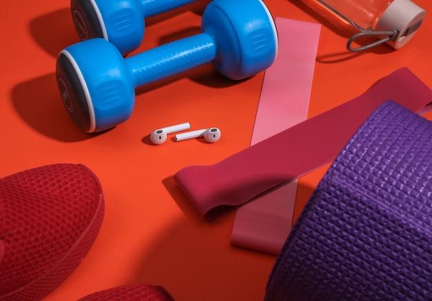 Akcesoria sportowe lub fitness na jasnym pomarańczowym tle.