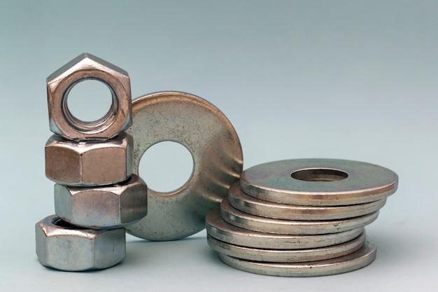 Akcesoria stolarskie. sterty metal śruby płuczki i dokrętki odizolowywający na białym tle.