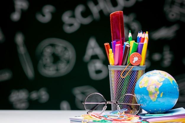 Akcesoria szkolne. książki, globus, ołówki i różne artykuły biurowe leżące na biurku