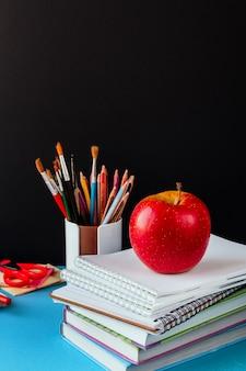 Akcesoria szkolne, notatnik, ołówki, markery, jabłko.