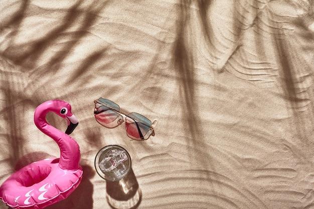 Akcesoria wakacyjne podróżnika są ułożone na białej plaży, piasek płasko ułożony widok z góry