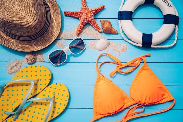 Akcesoria z kobietą na lato w podróży. na niebieskiej drewnianej podłodze