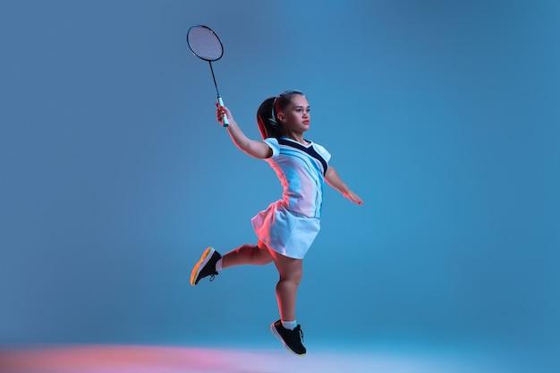 Akcja. piękna karłowata kobieta ćwicząca w badmintonie odizolowana na niebiesko w neonowym świetle