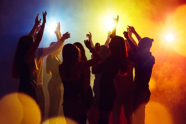 Akcja. tłum ludzi w sylwetce podnosi ręce na parkiecie na neonowym tle. życie nocne, klub, muzyka, taniec, ruch, młodzież. żółto-niebieskie kolory i poruszające dziewczyny i chłopcy.