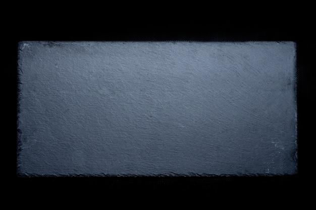 Akcyjna fotografia naturalny siwieje łupek na czarnym tle.