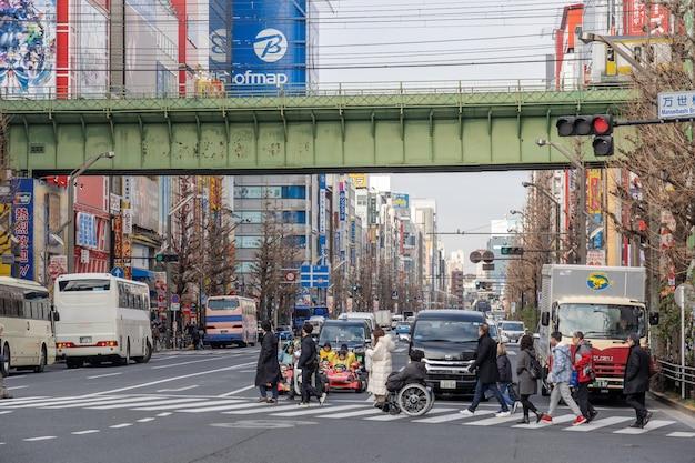Akihabara z tłumami niezdefiniowanych ludzi chodzących z wieloma budynkami w tokio, japonia.