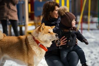 Akita-inu pies stoi przez kobietę z małym synem gra w parku