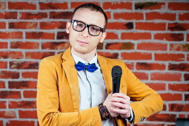Aktor mężczyzna (komik) w okularach, stylowym i krawatowym garniturze trzyma mikrofon. koncepcja wystąpień publicznych