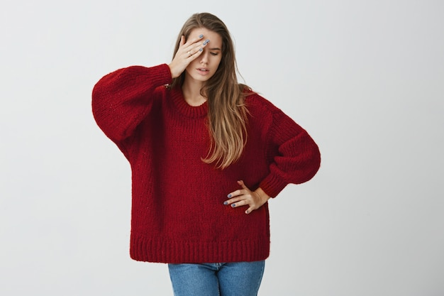 Aktorka umiera we mnie. portret uroczej studentki w modnym luźnym swetrze trzymającej dłoń na czole i odwracającej się do roli, grający w klubie dramatycznym, stojący