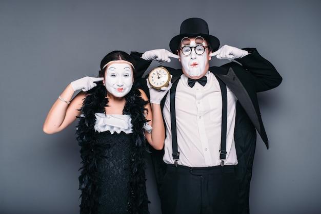 Aktorzy pantomimy występujący z budzikiem