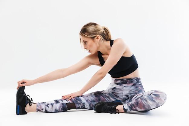 Aktywna blond kobieta w wieku 20 lat ubrana w odzież sportową ćwiczącą i rozciągającą ciało podczas aerobiku na białym tle nad białą ścianą