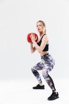 Aktywna blond kobieta w wieku 20 lat ubrana w odzież sportową, ćwicząca i wykonująca ćwiczenia z piłką fitness podczas aerobiku na białym tle nad białą ścianą