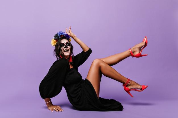 Aktywna dama w koronie z niebieskich kwiatów prezentuje stylowe szpilki w kolorze koralowym. portret figlarnej dziewczyny z maską czaszki siedzi na podłodze.
