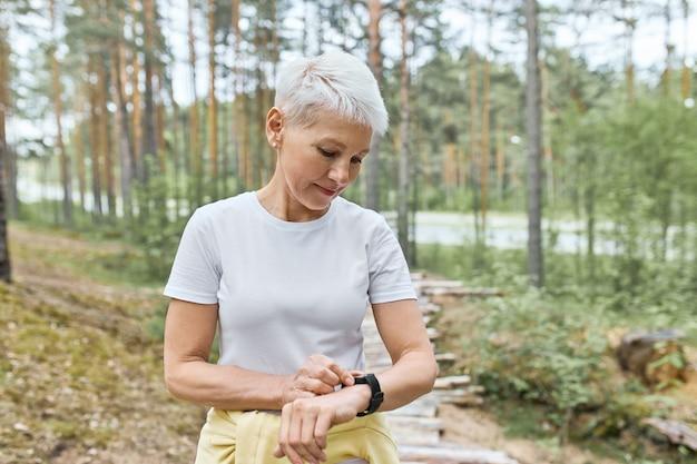 Aktywna dojrzała kobieta z krótkimi blond włosami pozuje na świeżym powietrzu, przygotowuje się do biegania, ustawia inteligentny zegarek, śledzi tętno i puls.