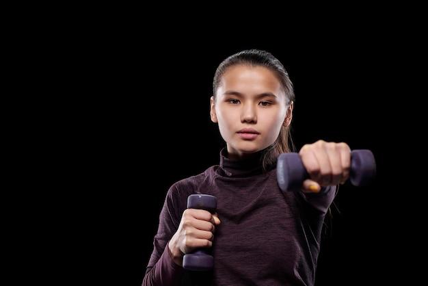 Aktywna dziewczyna sportowa z hantlami wyciągając ramię do przodu podczas ćwiczeń na czarnej ścianie