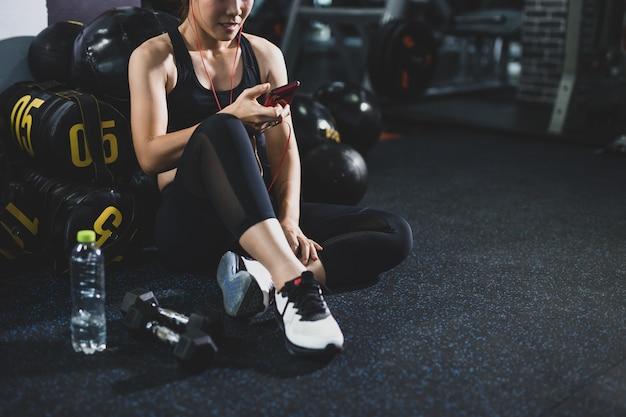 Aktywna dziewczyna używa smartphone w sprawności fizycznej gym. młoda kobieta trening w gym zdrowym stylu życia - wizerunek