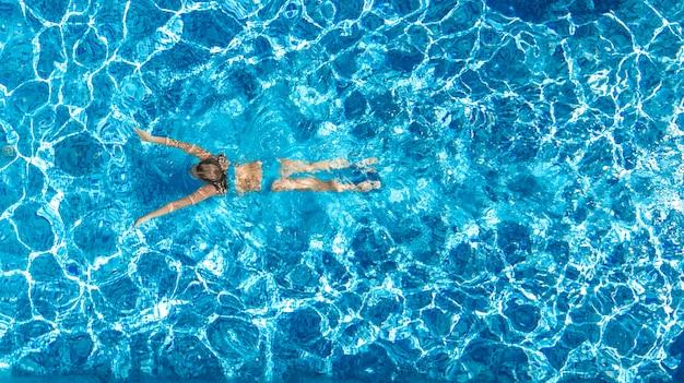 Aktywna dziewczyna w basenie widok z lotu ptaka drone z góry, młoda kobieta pływa w błękitne wody