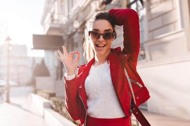 Aktywna dziewczyna w duże okulary przeciwsłoneczne, zabawy na ulicy
