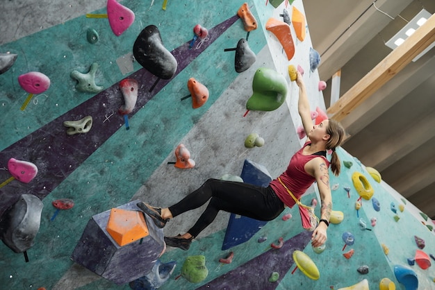 Aktywna dziewczyna w sportowej odzieży trzymająca się jednej z małych skałek w całym sprzęcie wspinaczkowym podczas wykonywania trudnych ćwiczeń