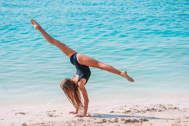 Aktywna dziewczynka na plaży, dużo zabawy. słodkie dziecko robi ćwiczenia sportowe nad brzegiem morza