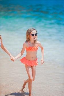 Aktywna dziewczynka na plaży świetnie się bawi na brzegu morza