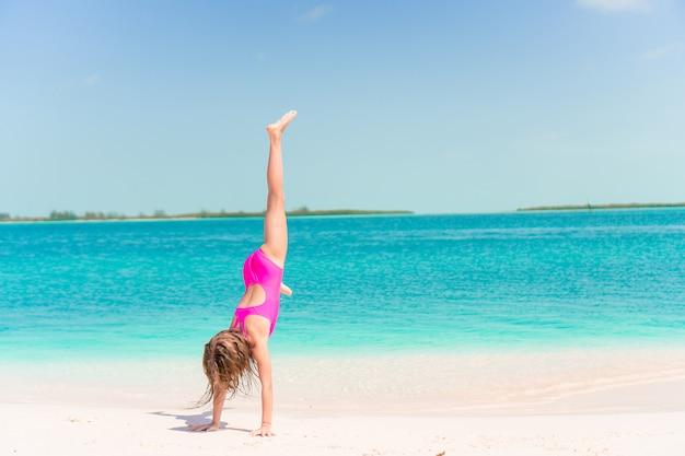 Aktywna dziewczynka na plaży świetnie się bawi na brzegu