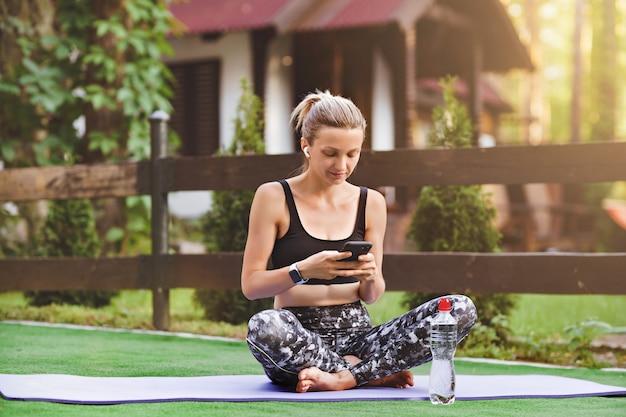 Aktywna energiczna sportsmenka siedząca na fioletowej macie, komentuje posty z telefonów komórkowych na zdrowych blogach sportowych na podwórku