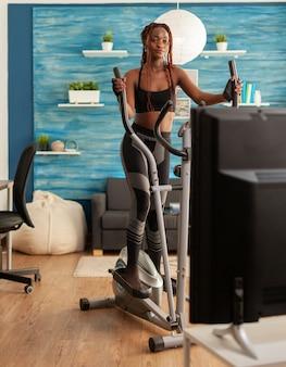 Aktywna fitness silna czarna kobieta biegająca na maszynie eliptycznej