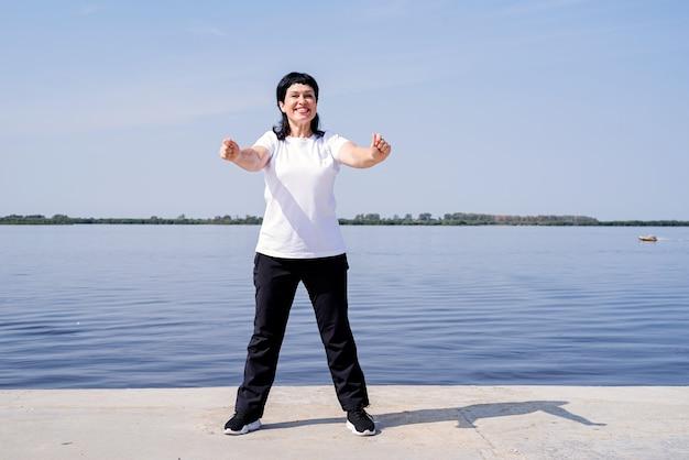 Aktywna i szczęśliwa starsza kobieta ćwiczy w pobliżu rzeki