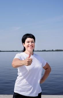 Aktywna i szczęśliwa starsza kobieta w odzieży sportowej pokazując kciuki do góry, pracując w pobliżu brzegu rzeki