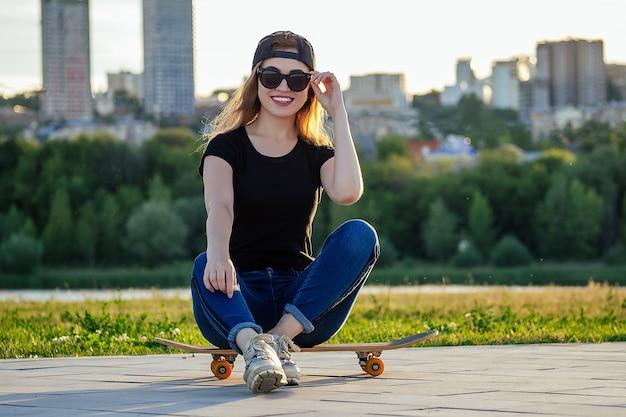 Aktywna jazda na łyżwach w letnim parku. piękna kobieta baw się z deskorolką (longboard) w tle rzeki miejskiego miasta. aktywny tryb życia wśród młodych ludzi