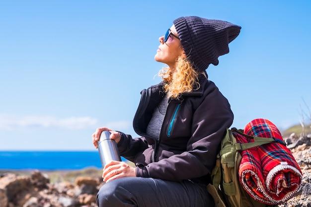 Aktywna kobieta kaukaski odpoczynek usiąść po trekkingowym spacerze -aktywność wypoczynku na świeżym powietrzu dla zdrowych ludzi -ocean. widok i błękitne niebo