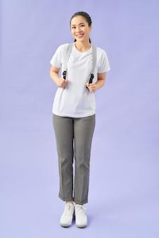 Aktywna kobieta na fioletowym tle, nosząca plecak i ciągnąca do przodu paski, uśmiechnięta przyjaźnie i otwarta