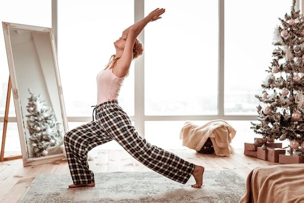 Aktywna kobieta rozpromieniona. sportowa długowłosa kobieta o porannym treningu w piżamie, z tyłu zaśnieżone miasto