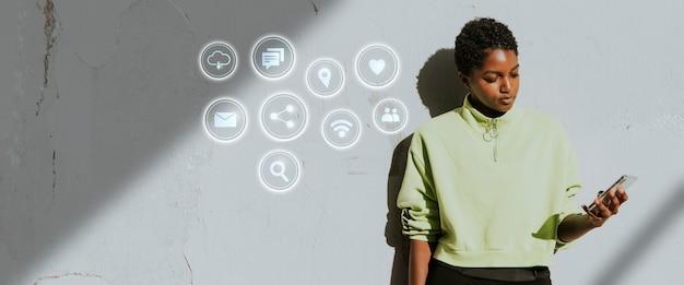 Aktywna kobieta stojąc przy ścianie i używając swojego smartfona
