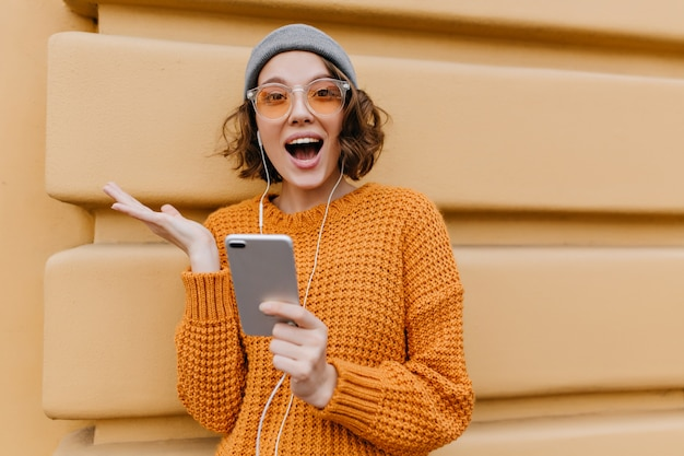 Aktywna kobieta w modnym, przytulnym stroju z wyrazem zadowolonej twarzy, trzymając smartfon
