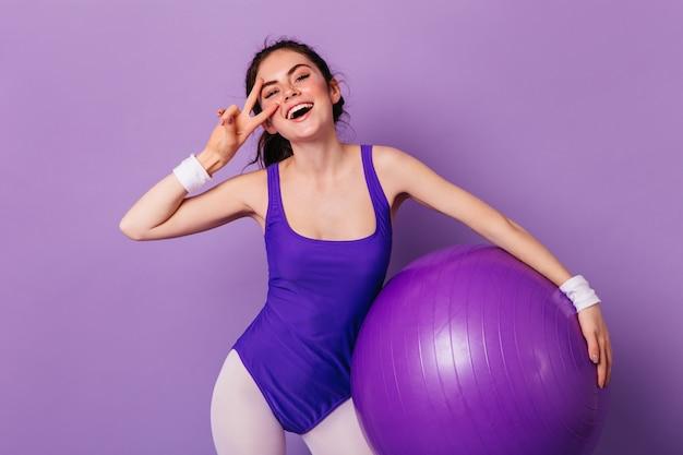 Aktywna kobieta w sportowym stroju w stylu lat 80. uśmiecha się i pokazuje znak pokoju