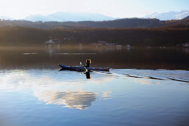 Aktywna kobieta wiosłuje na kajaku po jeziorze