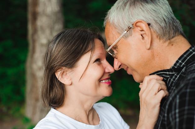 Aktywna kochająca starsza para chodzi w pięknym lato lesie