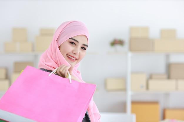 Aktywna mądrze azjatykcia muzułmańska kobieta w cajgowej kurtce stoi torba na zakupy i trzyma
