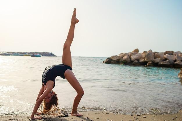 Aktywna mała dziewczynka ma dużo zabawy na plaży. słodkie dziecko robi ćwiczenia sportowe nad brzegiem morza
