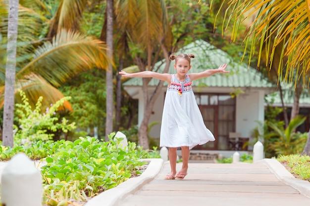Aktywna mała dziewczynka ma dużo zabawy na plaży.