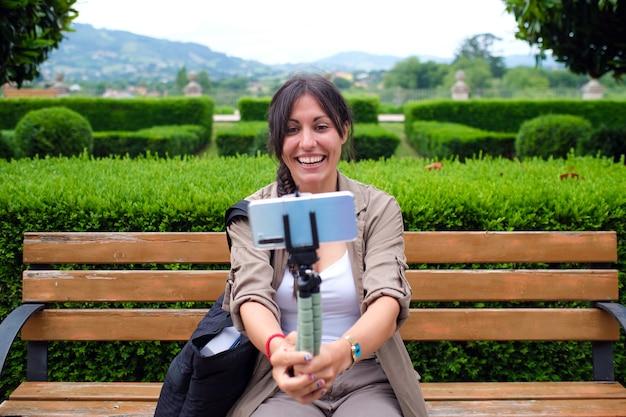Aktywna młoda dorosła kobieta przeprowadza wideorozmowę na zewnątrz, siedząc na ławce w parku, trzymając smartfon na statywie i rozmawiając z kamerą