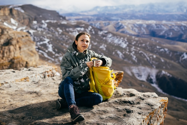 Aktywna młoda dziewczyna siedzi na skraju góry, z żółtym plecakiem, cieszy się górską przyrodą i słońcem