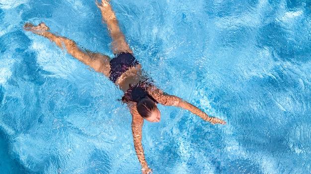 Aktywna młoda dziewczyna w basenie widok z lotu ptaka z góry młoda kobieta pływa w niebieskiej wodzie