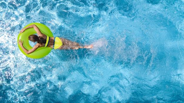 Aktywna młoda dziewczyna w basenie z lotu ptaka dziecko relaksuje się i pływa na dmuchanym kółku